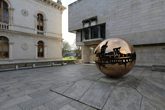 DUBLIN, IRELAND - Mar 24, 2021: Berkeley Library Building with in entrance the sculpture of the artist Pomodoro.