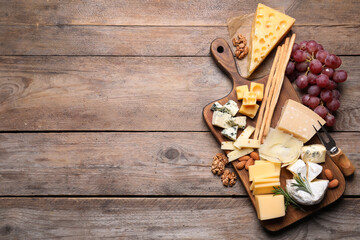 Cheese plate with grapes and nuts on wooden table, top view. Space for text