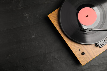 Fototapeta Turntable with vinyl record on black background, top view. Space for text