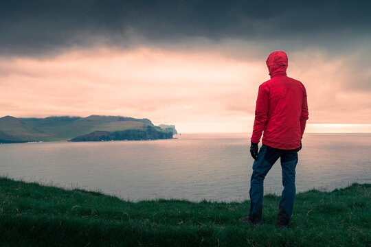 man in red jacket looking out over cliffs at Eysturoy in sunset, Faroe Islands.