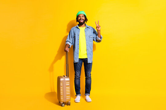 Full size photo of young positive smiling afro man showing v-sign holding luggage isolated on yellow color background
