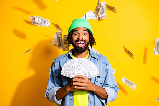 Photo of young handsome happy cheerful excited man winning lot of money in lottery isolated on yellow color background