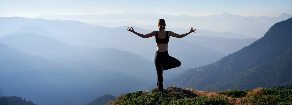 Silhouette of young woman performing yoga pose on grassy hill and looking at beautiful mountains. Sporty woman standing on one leg while practicing yoga outdoors in the morning.