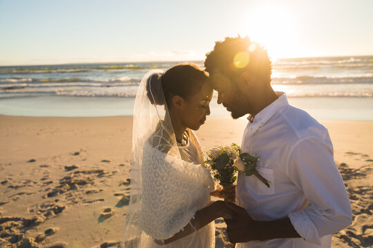 African american couple in love getting married on beach touching foreheads
