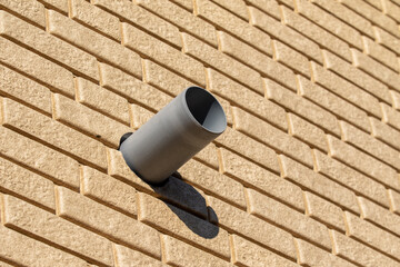 plastic pipe on the side of a brick wall