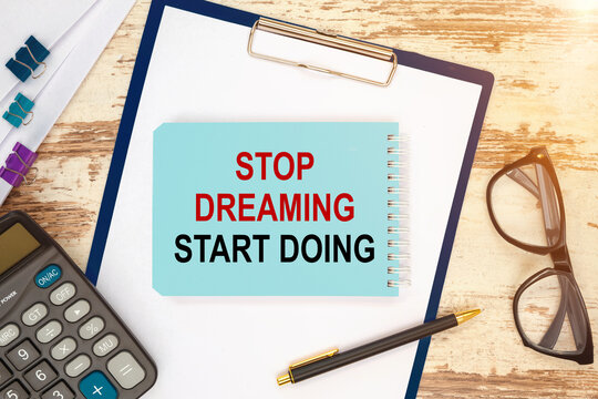 Notebook with text - Stop Dreaming Start Doing, near office supplies.