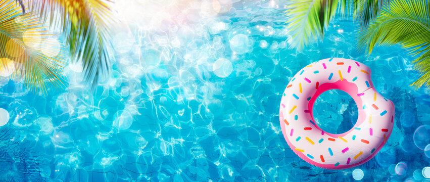 Inflatable Donut In Pool With Palm Leaves And Sunlight