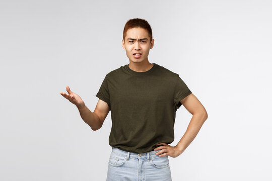 So what, why. Portrait of displeased angry asian man look frustrated and bothered, raising hand in dismay and shrugging, dealing with rude person, whats your problem, arguing, grey background