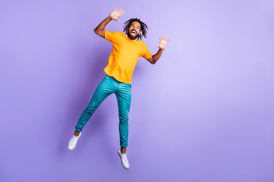 Full size photo of nice optimistic brunette hairdo guy jump wear orange t-shirt pants isolated on lilac color background