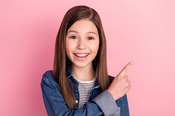 Photo portrait of small girl pointing finger on blank space isolated on pastel pink color background Wall mural