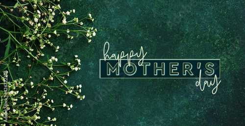 Dark green floral background with Happy Mother's day graphic text for holiday of mom.