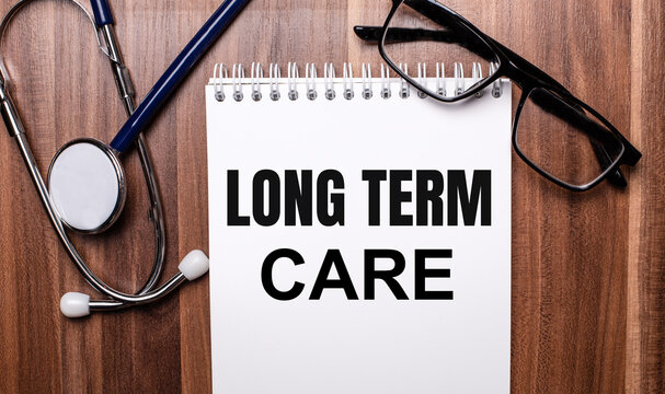 The words LONG TERM CARE is written on white paper on a wooden background near a stethoscope and black-framed glasses. Medical concept