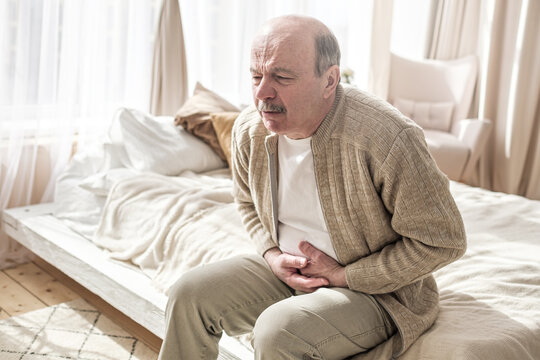 Elderly man with bellyache holding stomach with his hand
