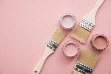 Overhead view of a DIY paint brush with pastel pink sample paint pots