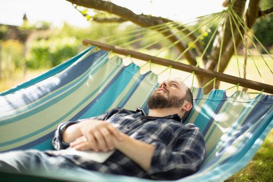 Serene man relaxing in sunny summer hammock