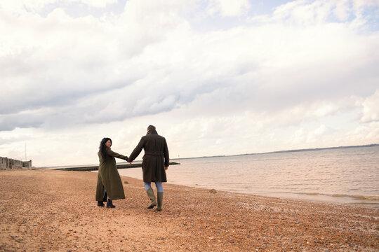 Couple in winter coats holding hands walking on ocean beach