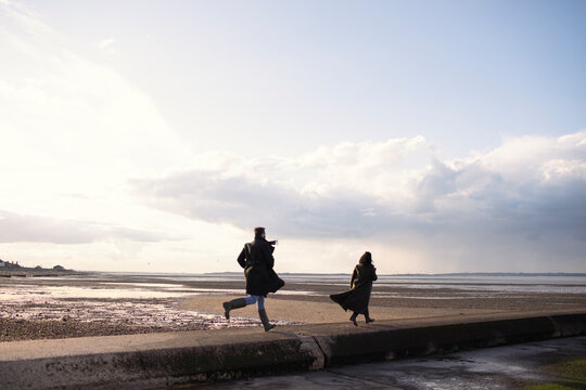 Couple in winter coats running on sunny ocean beach jetty