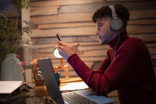 Young man with headphones working at home with smart phone and laptop