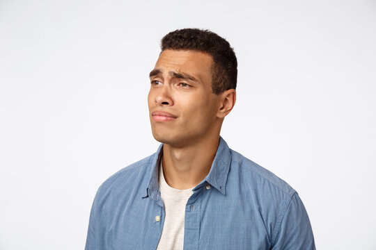 Man feeling regret, missing something interesting, dont have money, cant afford something. Disappointed gloomy, sad hispanic guy looking left, frowning express jealousy and sadness, white background