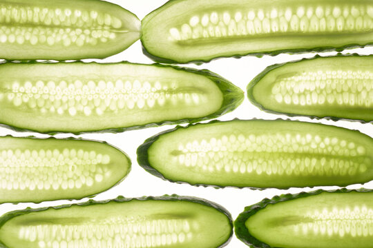 Cucumber green slices pattern isolated on white background. Creative cucumbers wallpaper, food backdrop design