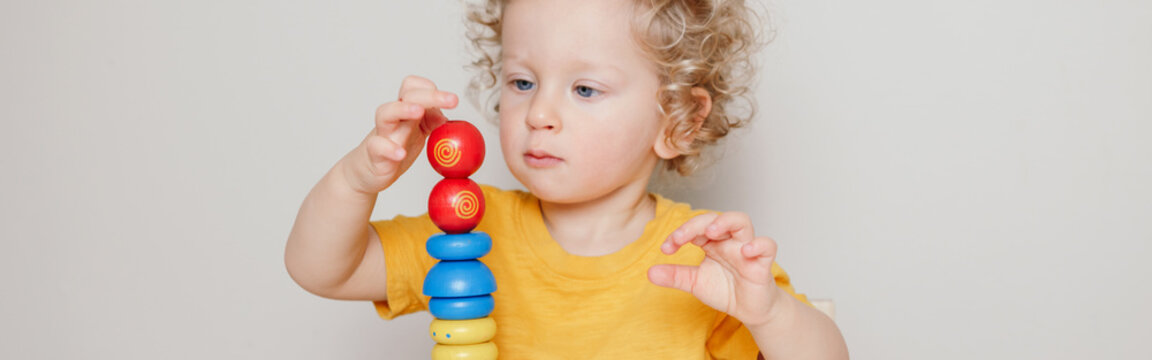 Cute baby toddler playing with learning toy pyramid stacking blocks at home or kindergarten. Early age Montessori education. Kids hand brain fun development activity. Web banner header.