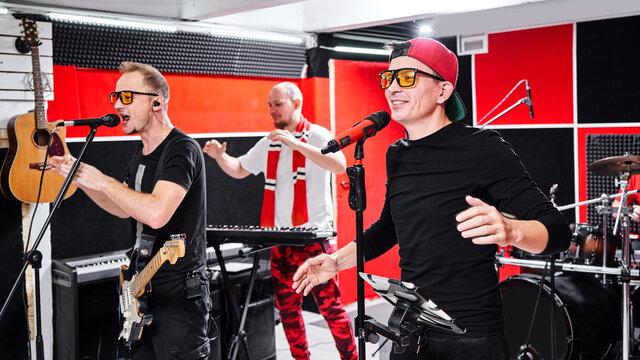 Modern music group at rehearsal base, recording track album