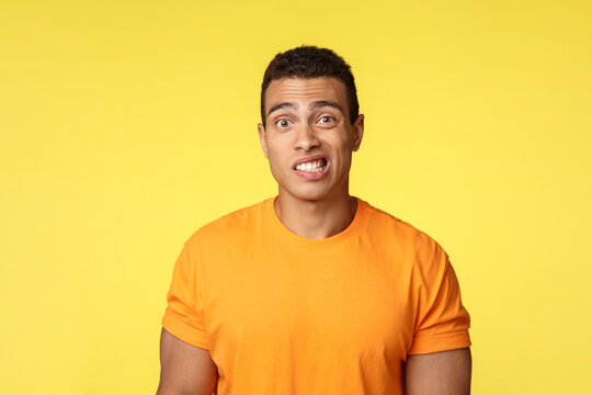 Yikes, awkward. Embarrassed young handsome man caught on lie, feel indesicive and slightly worried, cringe, smiling nervously and look camera with reluctance, stand yellow background