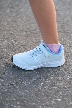 female foot in white sport shoe