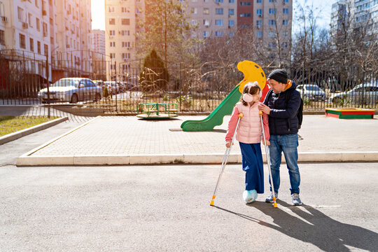 dad helps daughter learn to walk on crutches. plaster on your feet.