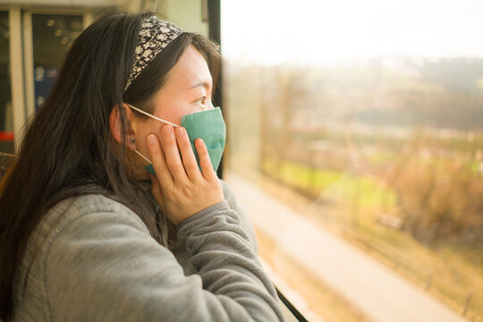 train travel in times of covid19 - young happy and cute Asian Korean woman in  face mask traveling on railcar looking landscape through the window enjoying holiday getaway