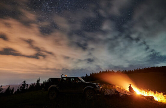 Wide angle view on cloudy starry night in the mountains and a man enjoying nature, sitting on logs in front of fire, off road car behind him. Concept of astrophotography, traveling and extreme ride