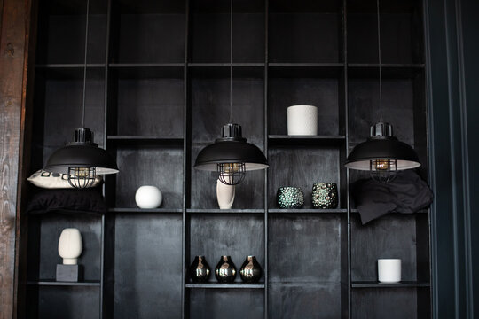 Metal chandeliers in retro style on background wooden shelves with decor. Dark room with Three modern lamps over table. Three modern black ceiling lamps hang in room, close-up. Loft room interior.
