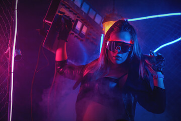 Young girl is dancing in the neon lights on the dance floor.