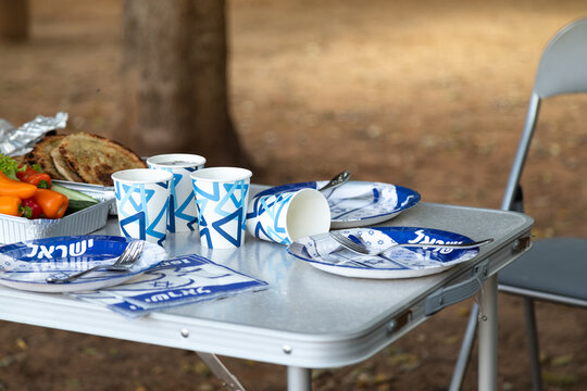 Folding furniture for a picnic in the forest. The table covered with disposable dishes with the symbols of Israel (with the inscription Israel in Hebrew). Yom Haatzmaut (Israel Independence Day)