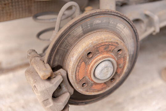 Heavily worn brake disc. Car brake disc after removing the wheel. A rusty disk that needs to be replaced.