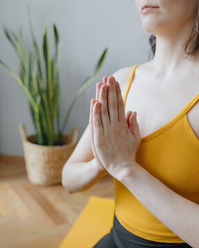 European caucasian woman practicing yoga and meditation in her home, home calming yoga on a yellow mat. millennial woman is into exercise and harmony within herself, lighting an aroma stick and doing