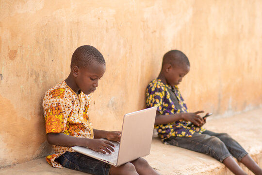 one african kid using a laptop and the other using a mobile phone