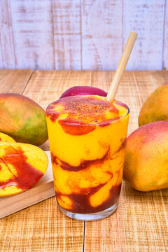 chamoyada or mango smoothie with chamoy and a bamboo straw, a refreshing mexican drink. served with mangoes and chamoy on a wooden table with a white wooden plank backdrop.