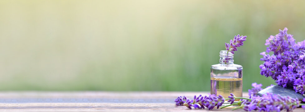 bottle of essential oil and  lavender flowers arranged on a wooden table on blur background