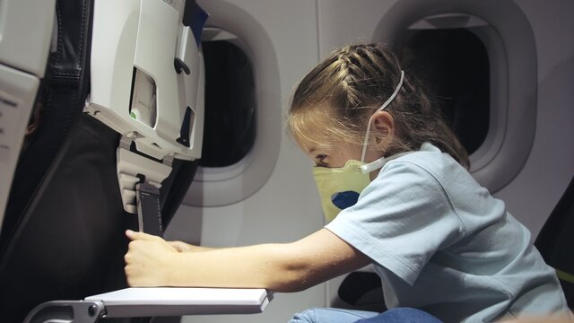 Little girl caucasian at plane with wearing protective mask. Child baby tourist at aircraft with respirator play at smartphone mobile. Covid-19.
