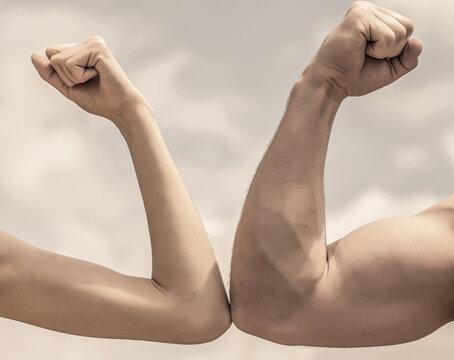 Muscular arm vs weak hand. Vs, fight hard. Competition, strength comparison. Rivalry concept. Hand, man arm fist Close-up. Rivalry, vs, challenge, strength comparison. Sporty man and woman