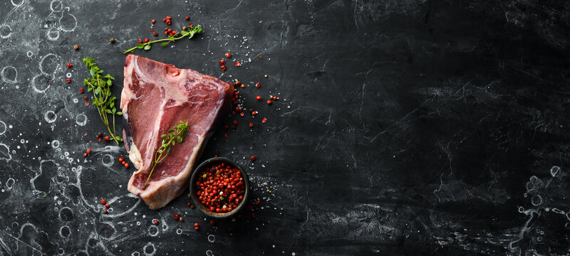 Raw aged T-bone steak on a black stone background. Top view. Rustic style.