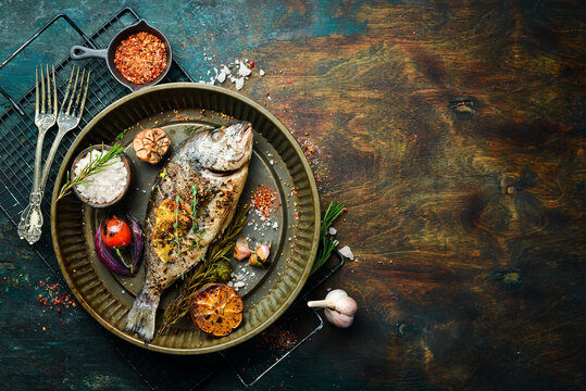 Baked dorado fish with asparagus and vegetables in a metal tray. Free copy space. On a black stone background.
