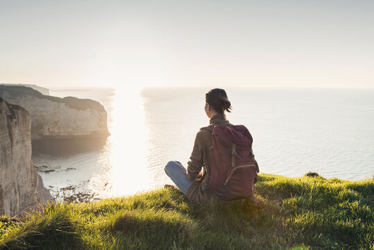 Young woman traveler with backpack sitting and looking at sunset above a sea over beautiful cliffs background, Travel, active lifestyle and summer holiday concept