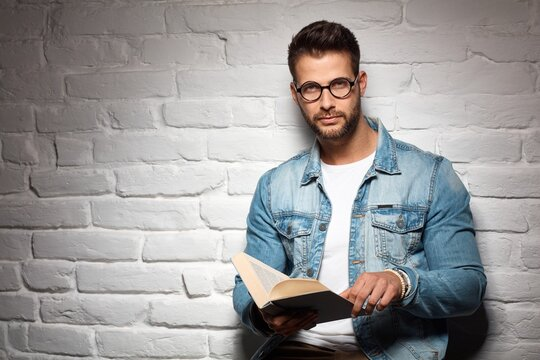 Smart casual man in glasses reading book, leading against brick wall. Copyspace.