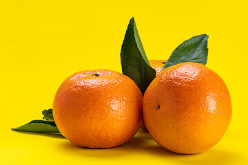 Fototapete - Side view of oranges with leaves isolated on yellow background with clipping path