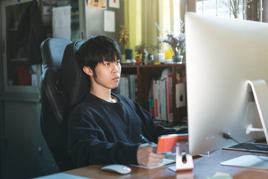 Freelancer young adult asian businessman working at home office.