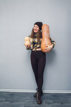 cheerful girl holding large and small pumpkin on gray background.