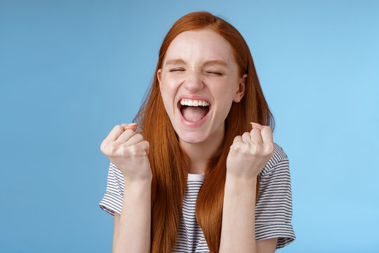 Yes achievement goal lifetime. Smiling happy european redhead girl raising clenched fists cheerful rejoicing yelling yeah accomplish goal success triumphing victory, great news win lottery
