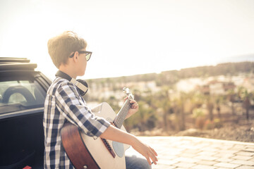 Fototapeta Young boy playing acoustic guitar sitting on the car trunk outdoors. Musician singing on the road looking at the panorama Teen learning to play musical instrument. Educational freedom carefree concept